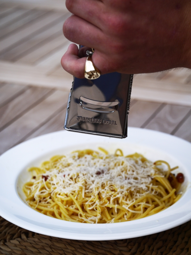 grating parmesan onto spaghetti carbonara